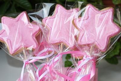 Galletas decoradas varitas mágicas de color rosa.